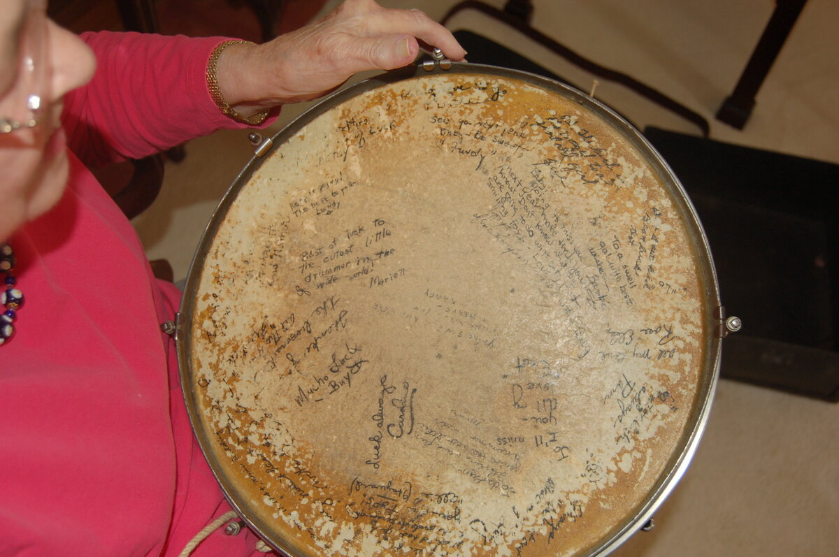 """To a swell gal with best wishes"" — Jo Singletary Barbre holds a snare drum signed by her fellow Darlinettes."