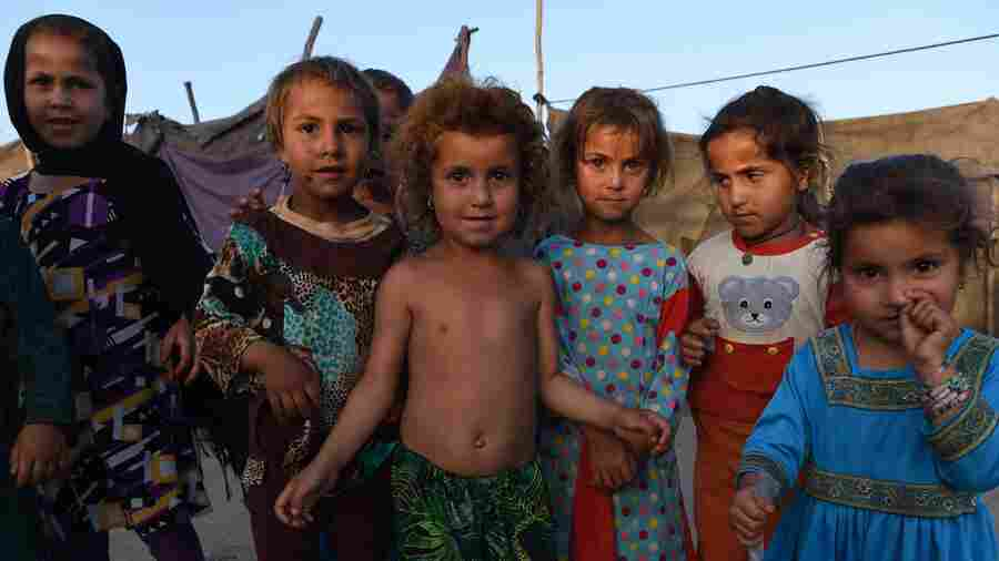 Afghan children look on at a refugee camp in Jalalabad on May 3. Like thousands of Afghan returnees, Neik Mohammad became unwanted in Pakistan after a Taliban massacre at a Peshawar school, forcing him to return home to a life of misery and fear in a squalid refugee settlement.
