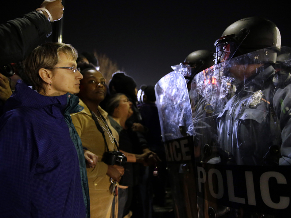 Police and protesters square off outside the Ferguson Police Department, in March.Earlier in the day, the resignation of Ferguson police chief Thomas Jackson was announced in the wake of a scathing Justice Department report prompted by the fatal shooting of an unarmed black 18-year-old by a white police officer. (Jeff Roberson/AP)