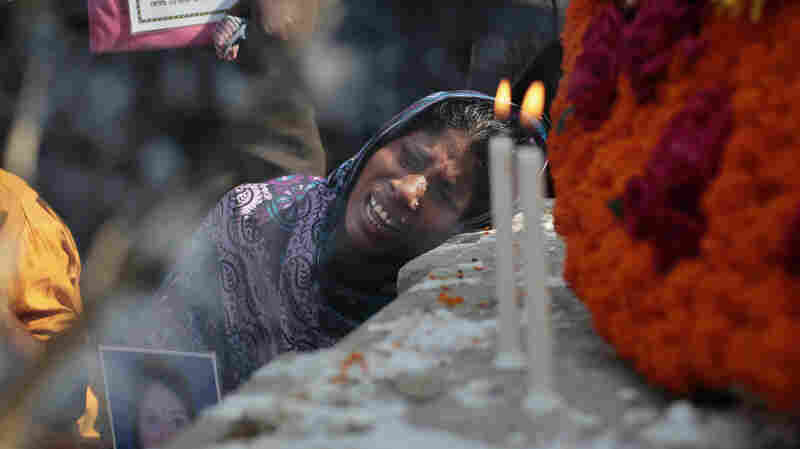 The relative of a worker who died in the 2013 Rana Plaza collapse mourns April 24 in front of a monument erected in memory of the victims. Authorities on Monday charged more than 40 people with murder in connection with the building's collapse that killed 1,137 people.