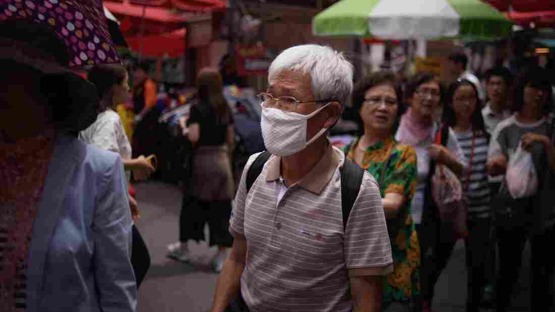 "A South Korean walks through a market in Seoul wearing a mask. South Korean President Park Geun-Hye scolded health officials over their ""insufficient"" response to an outbreak of the MERS virus."