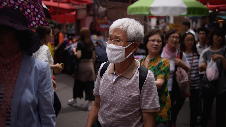 "A South Korean walks through a market in Seoul wearing a mask. South Korean President Park Geun-Hye scolded health officials over their ""insufficient"" response to an outbreak of the MERS virus. (Ed Jones/AFP/Getty Images)"