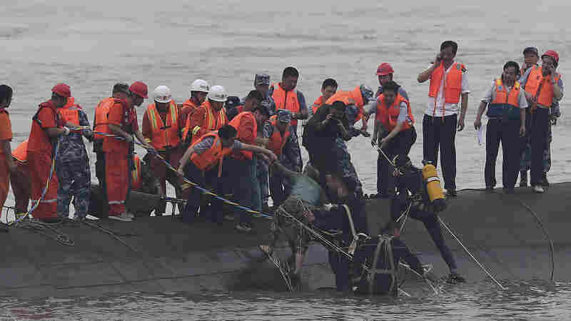 Rescuers pull a survivor from an overturned passenger ship in the Jianli section of the Yangtze River in central China's Hubei province on Tuesday.