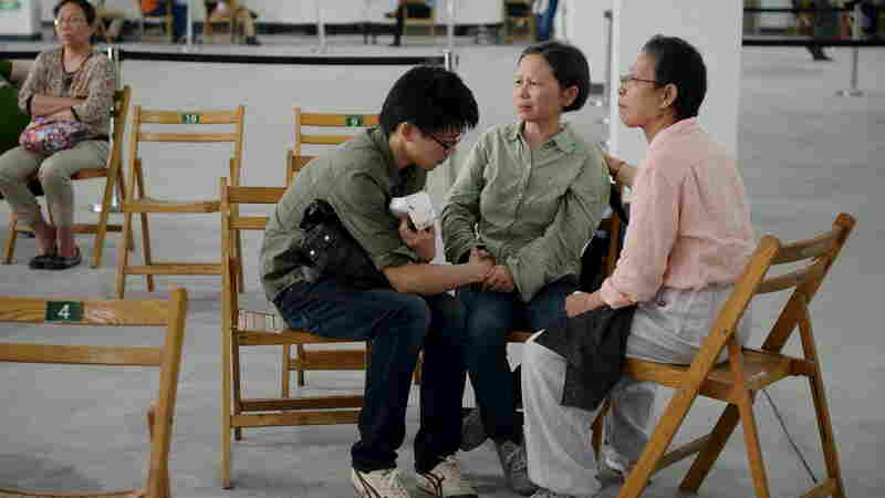 Relatives of passengers of the sunken Eastern Star cruise ship wait at a government arranged meeting point in Shanghai, China, Wednesday. Divers have searched the capsized ship in the Yangtze River for survivors; the ship held more than 450 people.