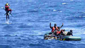 Spain's maritime rescue service saves African migrants from a rubber boat that capsized near Tarifa, southern Spain. A helicopter team lifts one man to safety, as others cling to the overturned raft in rough waters. All 11 people were rescued.