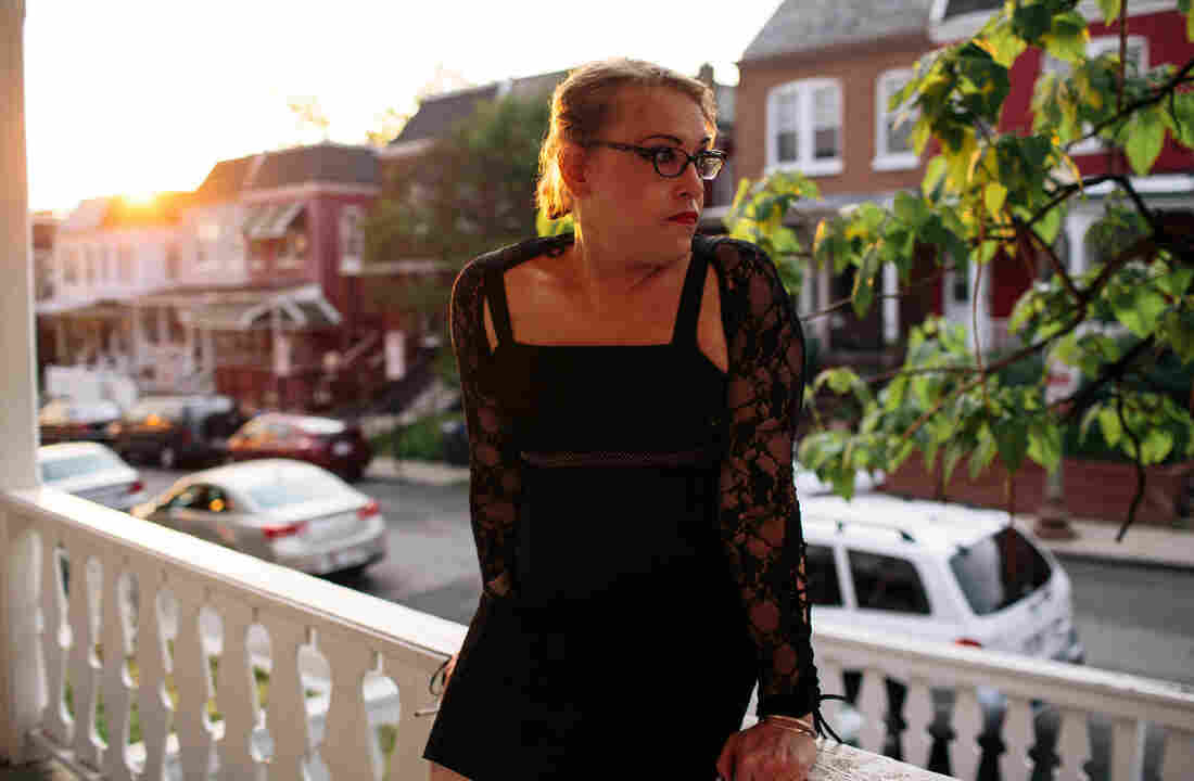 Kiera Atkins smokes on the porch of a transitional group home for transgender adults who are trying to get on their feet.