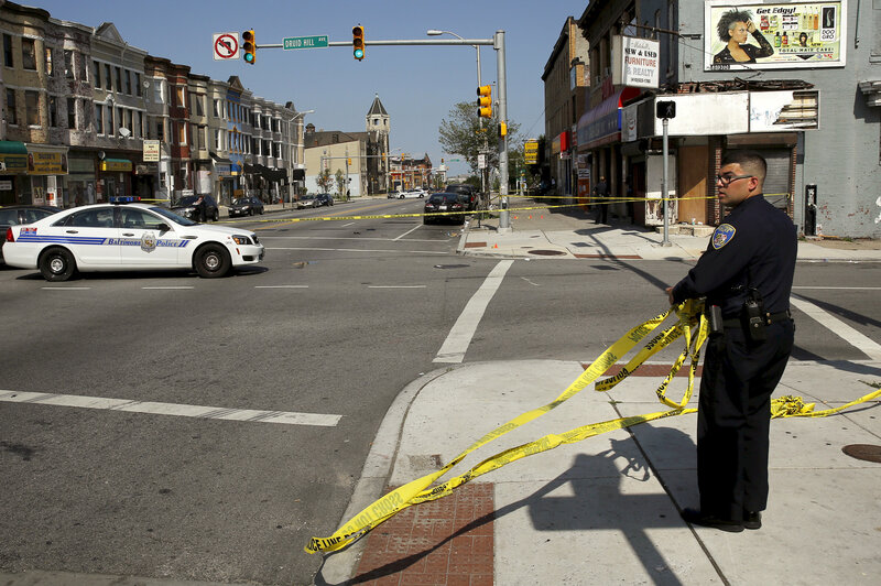 A Baltimore police officer attempts to secure a crime scene with tape at the scene of a shooting at the intersection of West North Avenue and Druid Hill Avenue in West Baltimore, Md., on May 30. Local media have reported more than 35 murders in the city since the April rioting over the death of 25-year-old resident Freddie Gray.