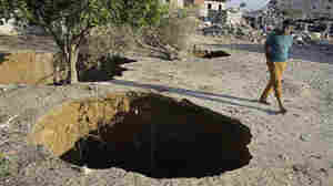 A young man walks by holes made by the Egyptian military to destroy smuggling tunnels connected to Gaza. The demolitions have put pressure on Hamas, the militant group that controls Gaza and has long counted on smuggling tunnels as its lifeline.