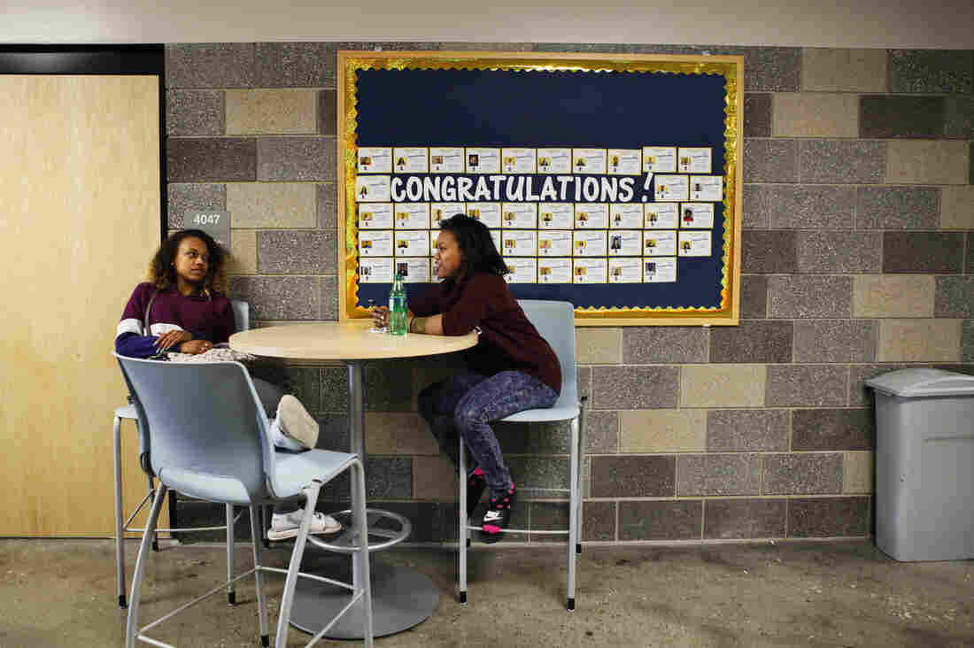 Students sit below a bulletin board of graduation notifications at Scavo Alternative High School in Des Moines, Iowa.