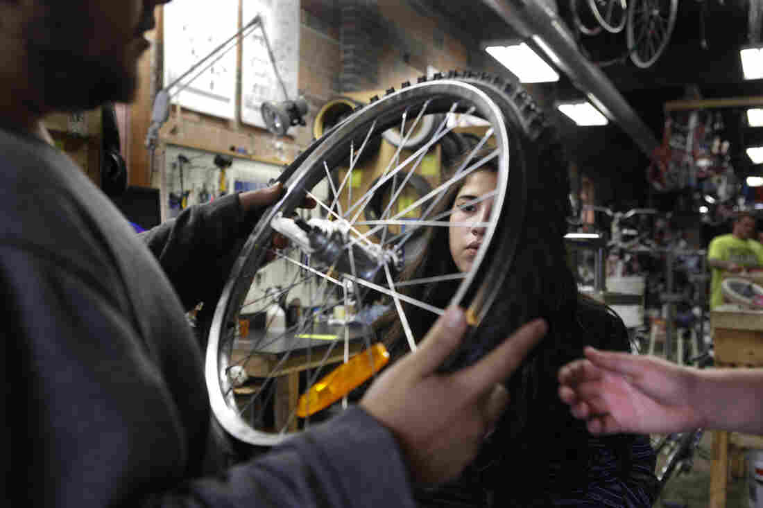 Scavo students change a tire during physics class at the Des Moines Bike Collective.