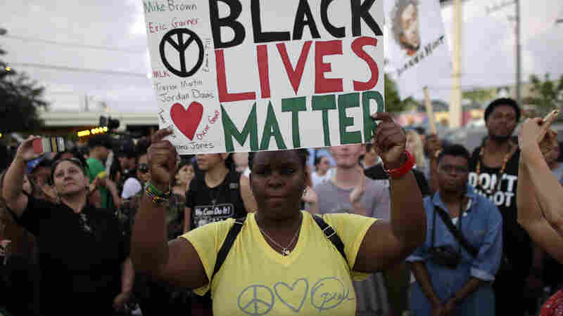 "Desiree Griffiths of Miami holds up a sign reading ""Black Lives Matter"" during a protest over the deaths of Michael Brown and Eric Garner."