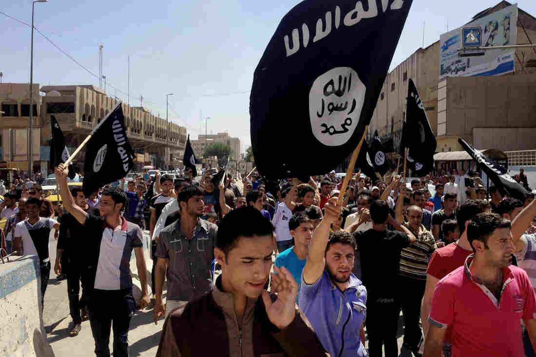 Demonstrators chant in favor of the Islamic State and carry the group's flag shortly after it took over Mosul in June 2014. The extremist group has fortified its hold on the city and few people are allowed to enter or to leave.
