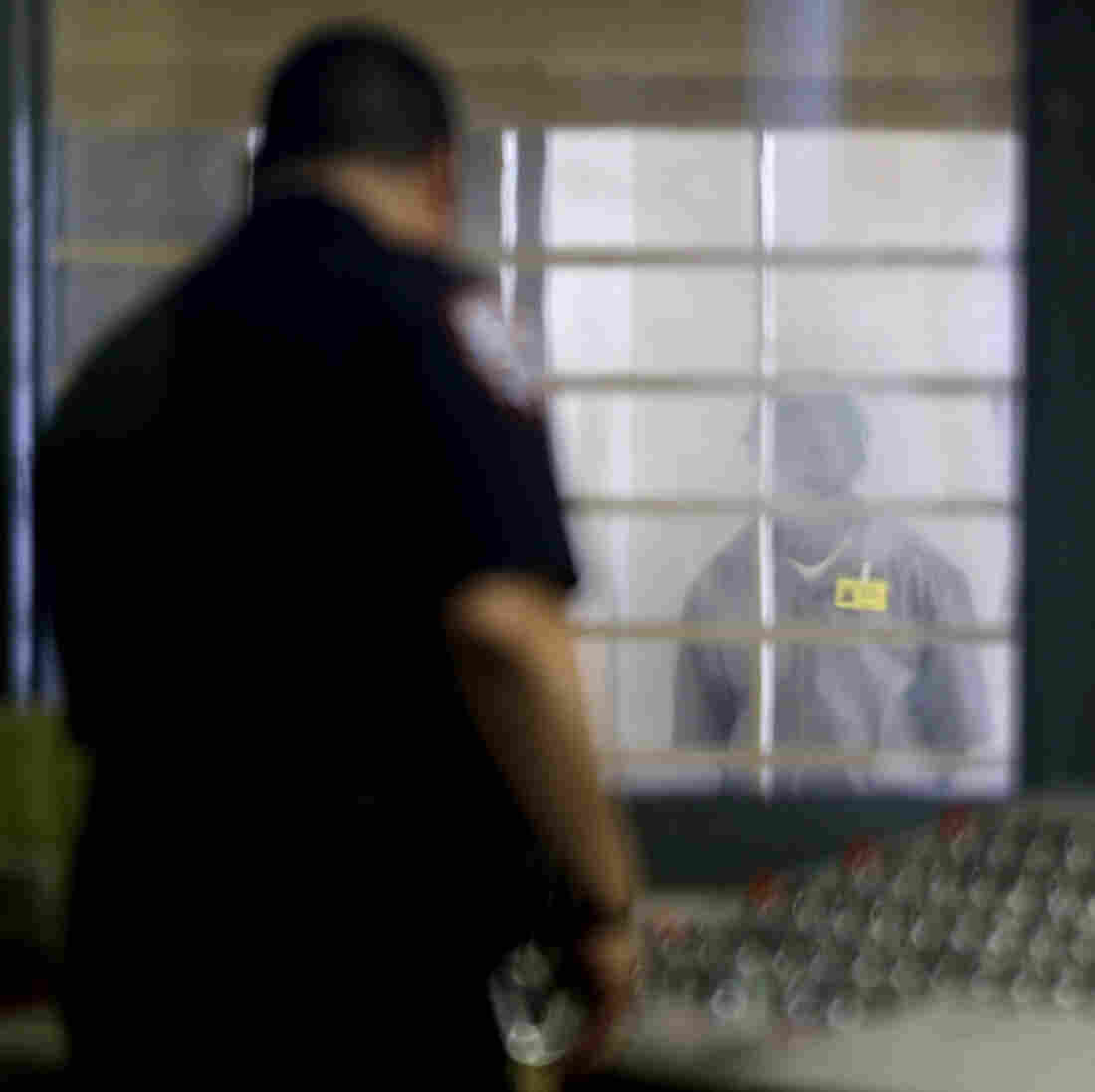 A prisoner behind bars and thick plastic looks at a corrections officer in an enhanced supervision housing unit on Rikers Island in New York.