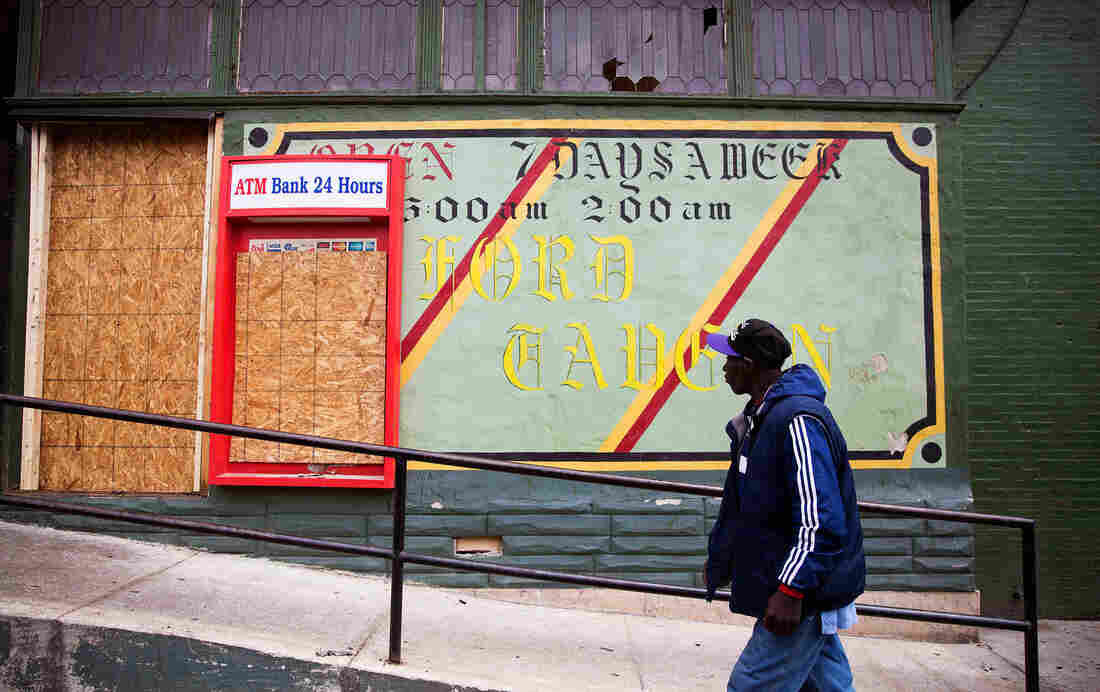 A man walks past the damaged Oxford Tavern on April 30 in Baltimore. Richard Sung Kang's liquor store and bar was hit by looters during a riot over the police-involved death of neighborhood resident Freddie Gray. The doors and windows were broken and cash and inventory stolen, leaving shelves bare.