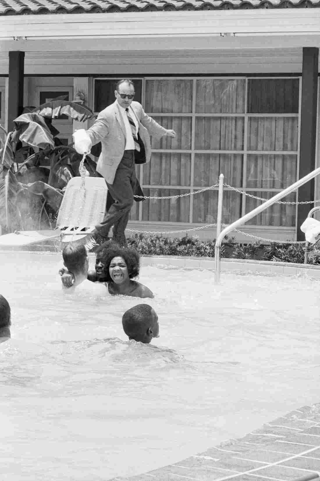 Protesters demonstrating in the swimming pool of the Monson Motor Lodge in St. Augustine, Fla., scream as motel manager James Brock dumps muriatic acid into the water on June 18, 1964.