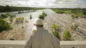 Tex Toler watches the Llano River rise Friday in Llano, Texas, after another round of heavy rains that have brought flooding and deaths to the state.