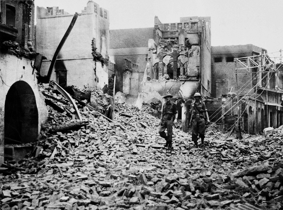 British Maj. T.J. Monaghan (left) and Pvt. H. Farabrother of the Inniskilling Regiment of Northern Ireland, walk through wreckage after riots destroyed parts of the Punjab suburb of Amritsar, India, in March 1947.