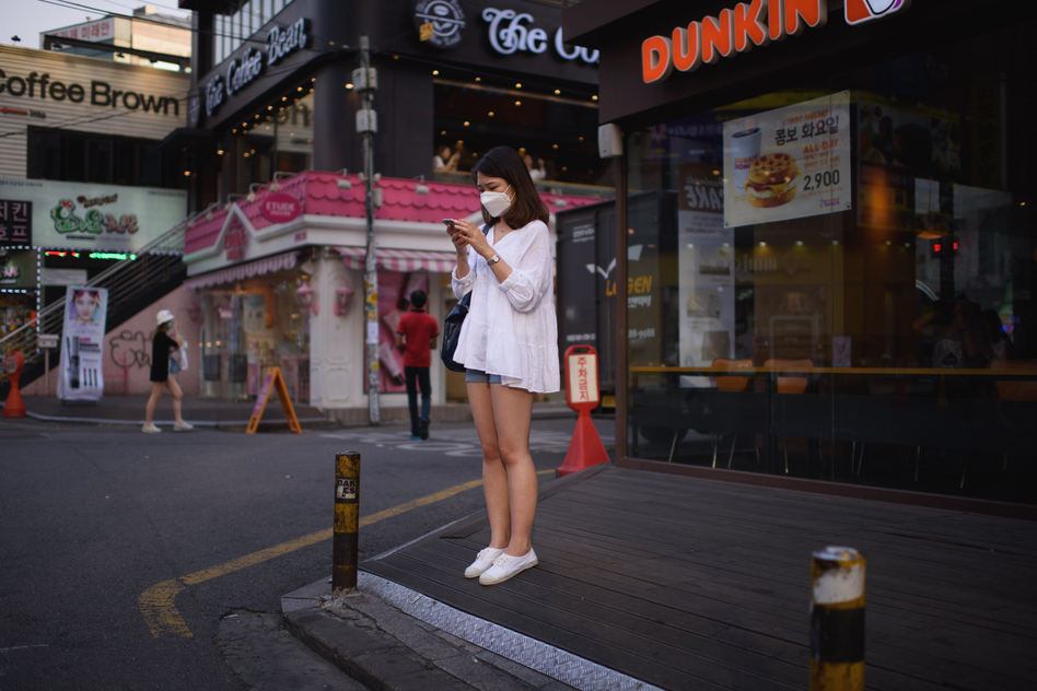 A woman on a street in Seoul checks her cellphone. The government is ramping up efforts to control an outbreak of the Middle East respiratory syndrome by monitoring the smartphones of those under quarantine. (Ed Jones/AFP/Getty Images)
