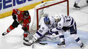 Chicago Blackhawks' Brandon Saad (left) reaches for a puck as Tampa Bay Lightning goalie Ben Bishop and Cedric Paquette (right) defend during the third period in Game 3 of the NHL hockey Stanley Cup Final on Monday.