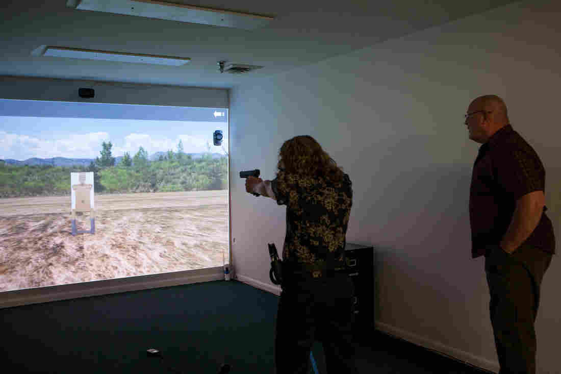 NPR reporter Carrie Johnson runs through a target practice drill with instructor Bryan Patterson as part of the Use of Force simulation at the Law Enforcement Legal Defense Fund in Virginia.