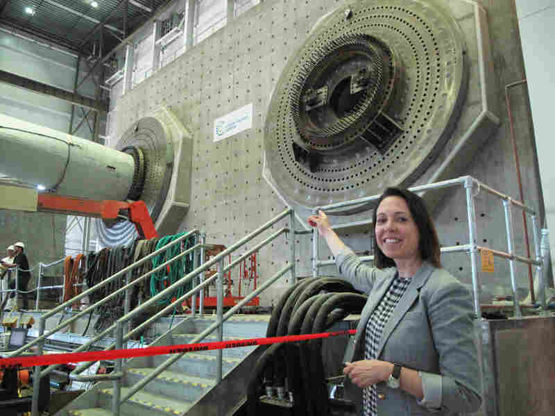 "Alicia Barton is the CEO of the Massachusetts Clean Energy Center. She's pointing at the massive steel and cement structure that supports the 100- to 200-foot-long blades at the testing center. Barton says the mission of this facility is ""to advance the state of wind energy technology in a way that will help that technology become more cost-effective over time."""