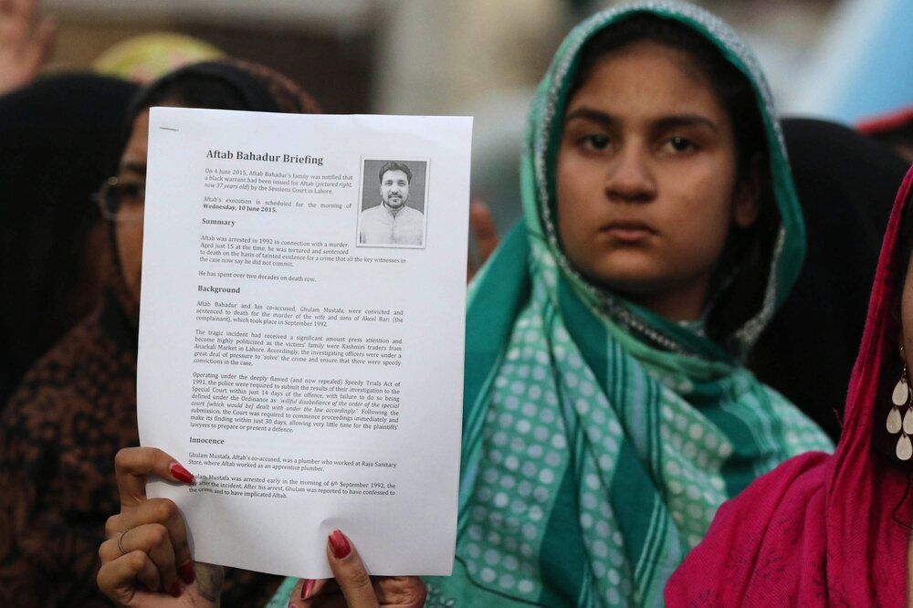 An unidentified relative of Aftab Bahadur shows a document with his photo during a news conference in Lahore, Pakistan, on Tuesday.