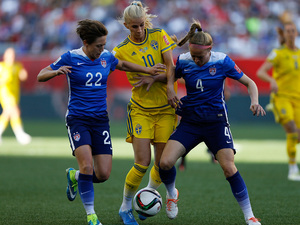 Defenders Meghan Klingenberg, left, and Becky Sauerbrunn of the United States sandwich Sofia Jakobsson of Sweden on Friday during their Group D World Cup match in Winnipeg, Canada.