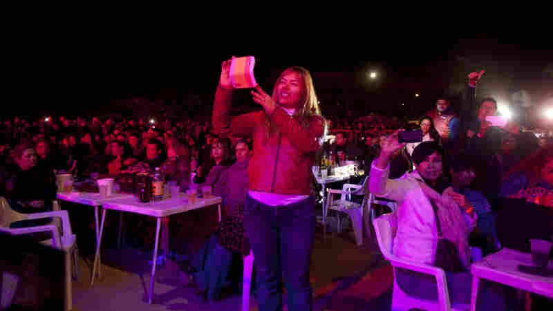 Concertgoers take photos of the band Intocable at a concert in Juarez, Mexico last year.