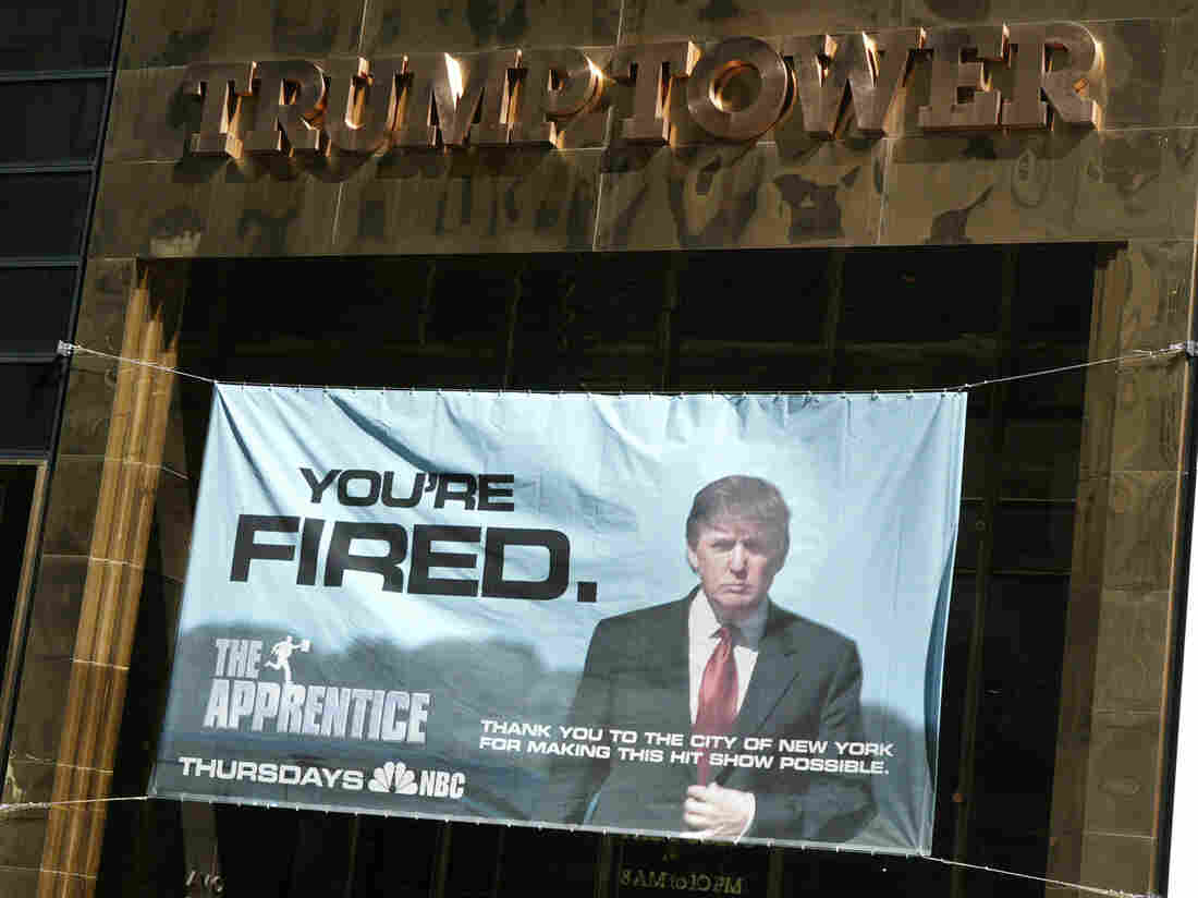 A sign advertising Trump's television show The Apprentice hangs at Trump Towers in New York City in 2004.