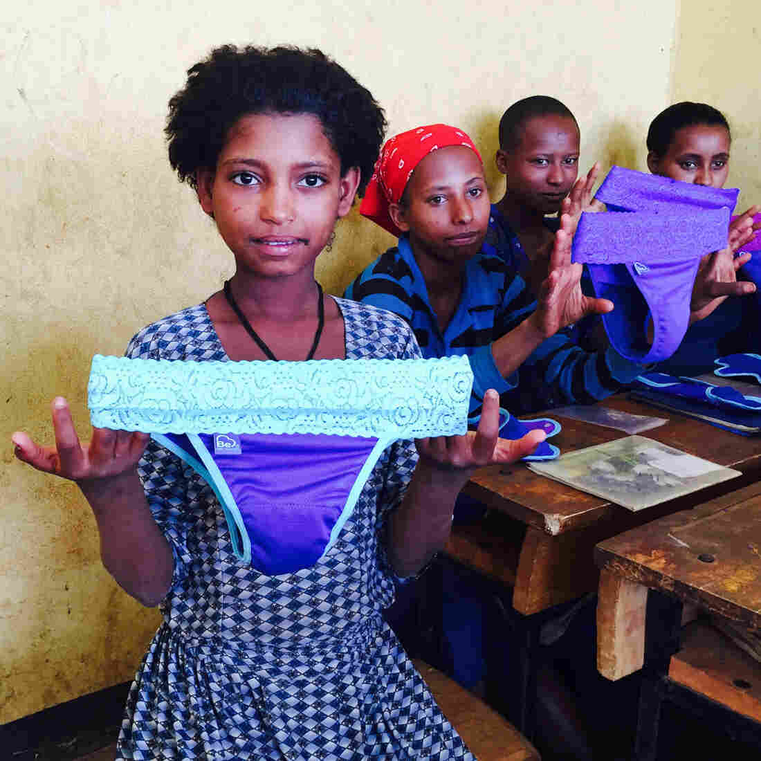 Schoolgirls in Ethiopia examine a new feminine product: underwear with a pocket for a menstrual pad.