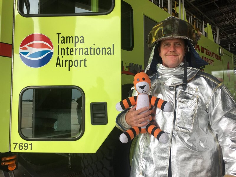 Hobbes poses for a photo with a member of the airport's tarmac emergency crew. The tiger was safely reunited with his young owner — along with a photo album of his exploits.