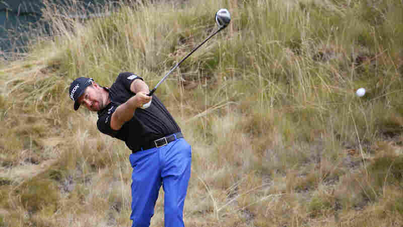 Graeme McDowell, of Northern Ireland, watches his tee shot on the sixth hole during the first round of the U.S. Open golf tournament at Chambers Bay. The brown grass may seem unusual to some American golf fans.