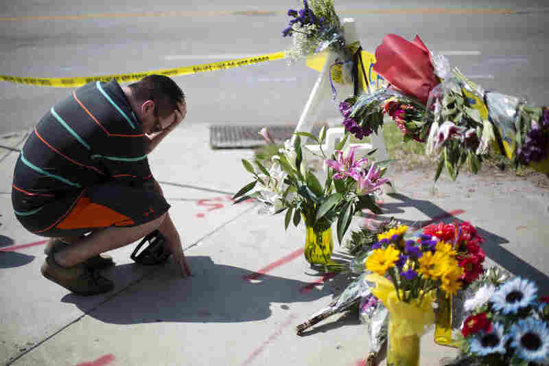 Noah Nicolaisen, of Charleston, S.C., kneels at a makeshift memorial for the victims of the shooting. Police apprehended the lone suspect during a traffic stop in Shelby, N.C., an almost four-hour drive from Charleston.