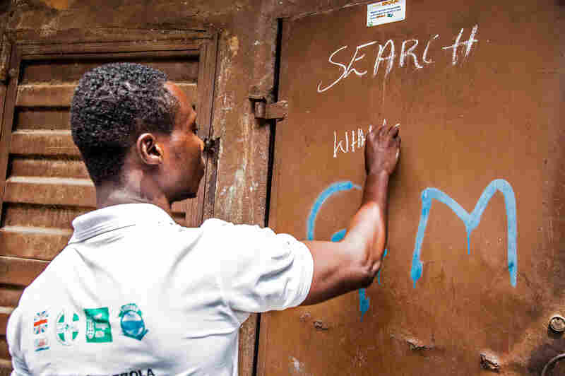 A health worker marks a house as free of Ebola while going door to door, looking for infected people in Freetown, Sierra Leone.