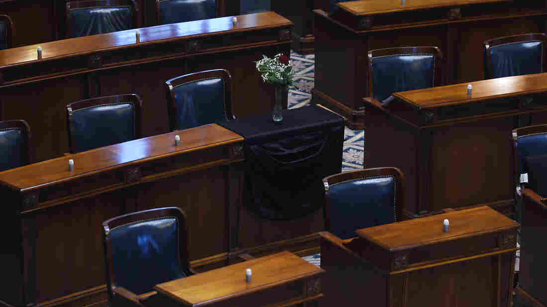 The desk of S.C. Sen. Clementa Pinckney is draped in black cloth with a single rose and vase in an empty chamber prior to a Senate session, Thursday, June 18, 2015, at the Statehouse in Columbia, S.C. Pinckney was killed, Wednesday in a shooting at an historic black church in Charleston.