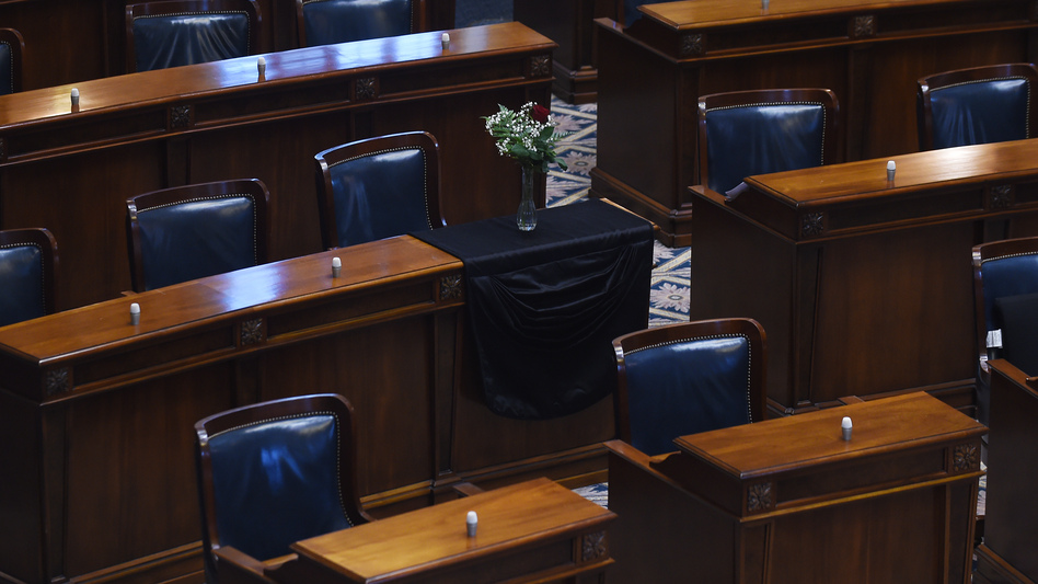 The desk of S.C. Sen. Clementa Pinckney is draped in black cloth with a single rose and vase in an empty chamber prior to a Senate session, Thursday, June 18, 2015, at the Statehouse in Columbia, S.C. Pinckney was killed, Wednesday in a shooting at an historic black church in Charleston. (Rainier Ehrhardt/AP)