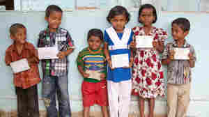 Children in Bangladesh display their birth registration cards.