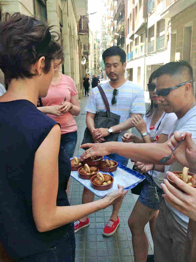 Tour guide Renée Christensen hands out tapas to tourists on her Devour Barcelona food tour. In this picture, tourists are sampling homemade meatballs in bean and pea gravy at La Botigueta del Bon Menjar, a local bar in Barcelona's Grácia neighborhood.