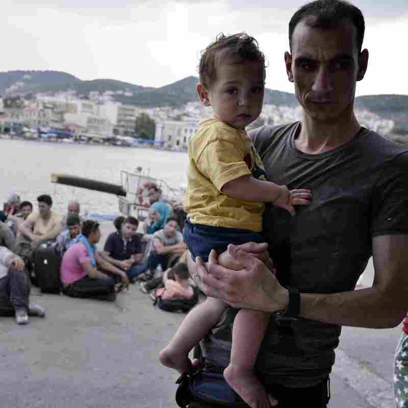Syrian refugees wait to be registered at the port of Mytilini in Greece following a 6km-long march.