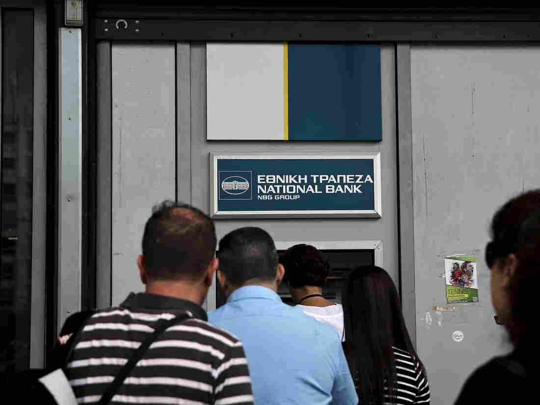 People line up at an ATM outside a National Bank branch in Athens last month. Greek bank deposits fell by $6.3 billion in April and on Friday, people withdrew more than $1 billion in a single day.