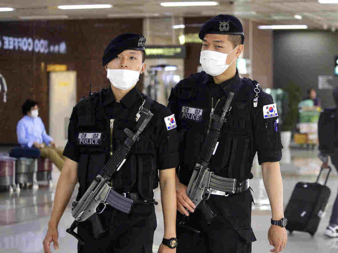 Airport guards go on patrol wearing masks at Gimpo International Airport in Seoul on Friday. South Korea has announced one more death, but no new cases of the Middle East Respiratory Syndrome coronavirus.