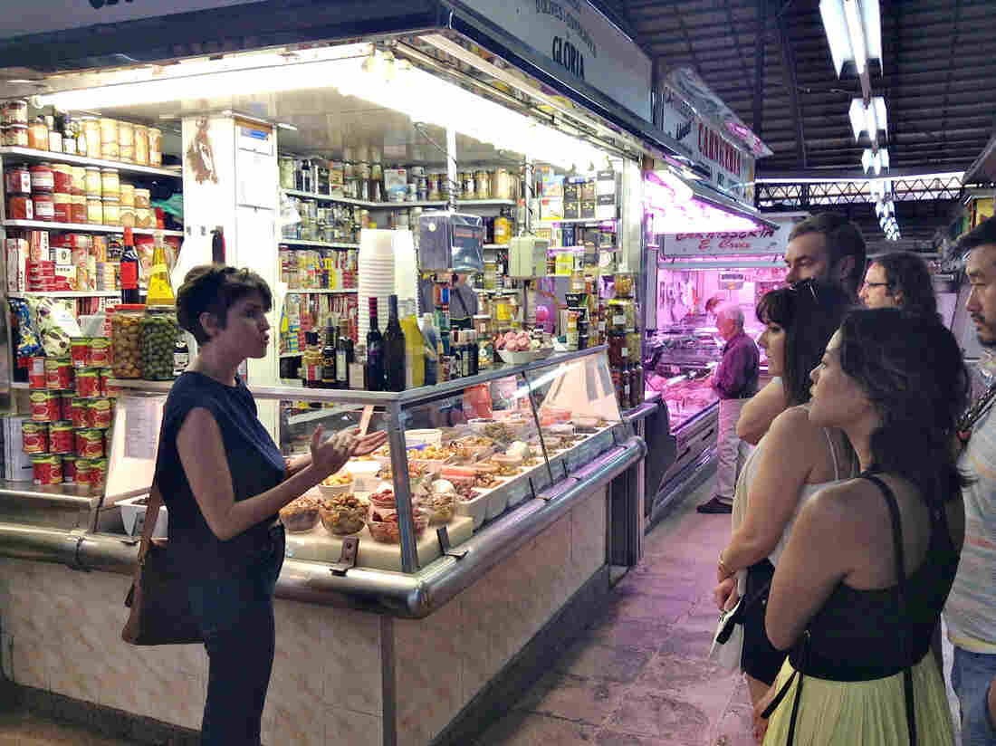 Christensen introduces tourists to Guiseppe the olive vendor at Barcelona's Mercat de l'Abaceria Central. Many of Devour Barcelona's clients return after the tour to buy more.