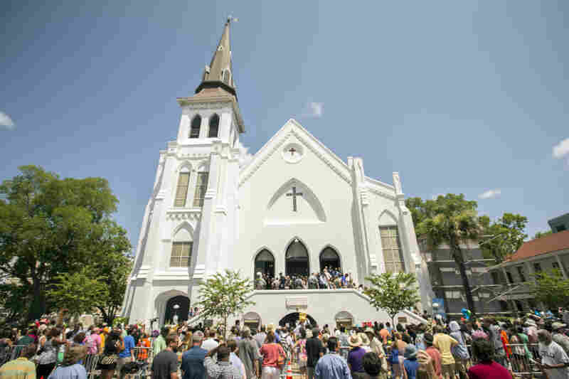 People stand outside as parishioners leave the Emanuel AME Church on Sunday.