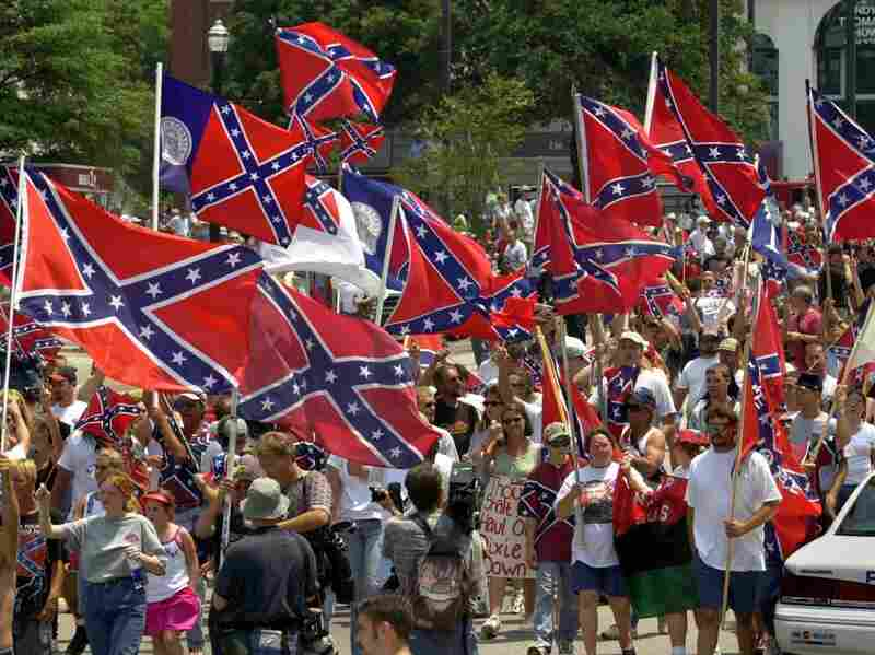 Demonstrators carry Confederate flags as they leave the entrance of the South Carolina Statehouse after the removal of the flag in Columbia, S.C., on July 1, 2000.