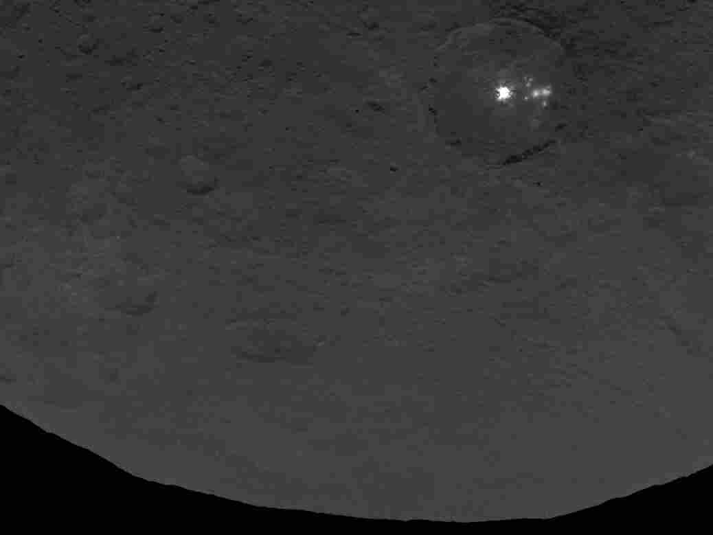 "A ""cluster of mysterious bright spots"" can be seen on the dwarf planet Ceres, NASA says. The image was taken by the Dawn spacecraft, in orbit of Ceres."