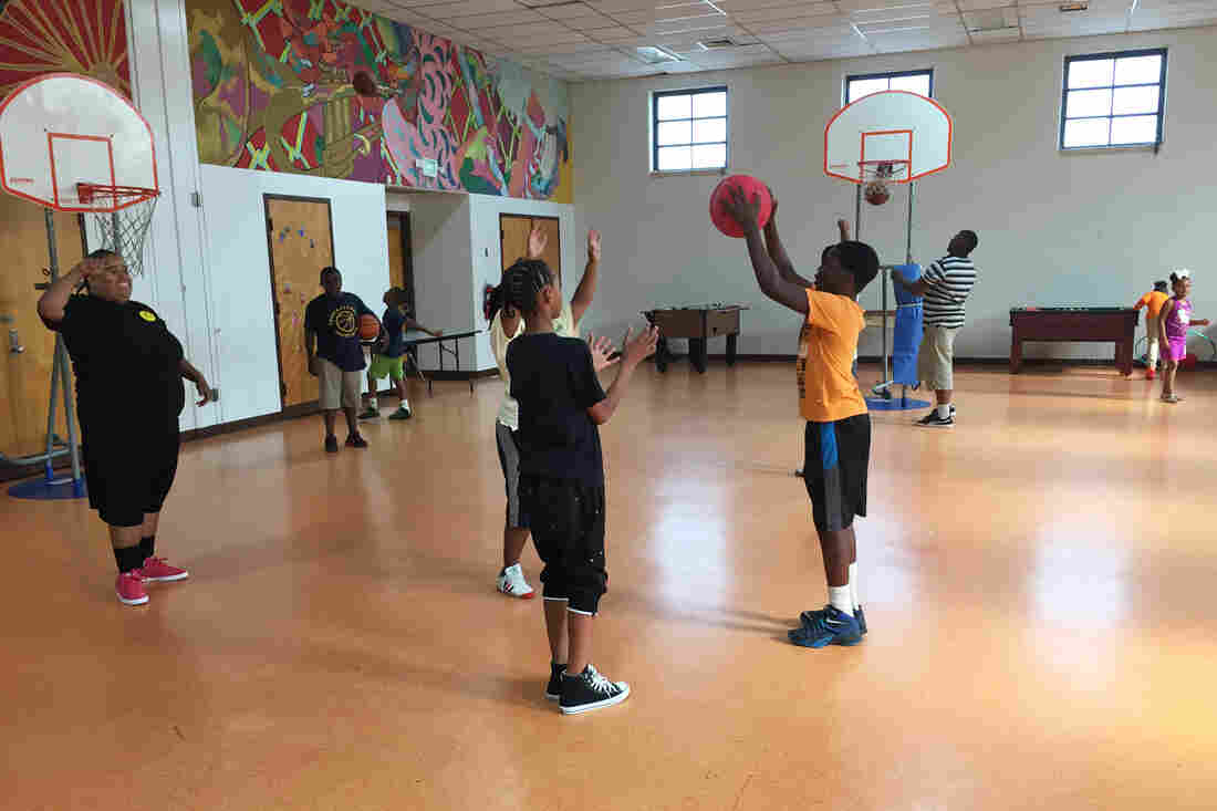 """Zyon Height (in orange) passes the ball during a game of basketball at the Lillian S. Jones Recreation Center. """"We are mom, dad, aunt, cousin,"""" says Brandi Murphy, the center's director. """"They come here to get what they don't have at home."""""""