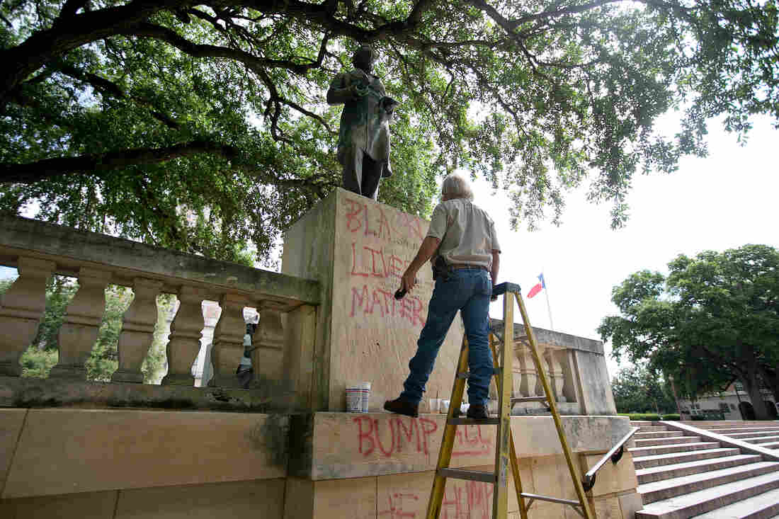 Bill Tanner works to remove graffiti from a statue of Jefferson Davis at the University of Texas in Austin. The statue is one of several around the country that have been targeted by vandals in recent days.