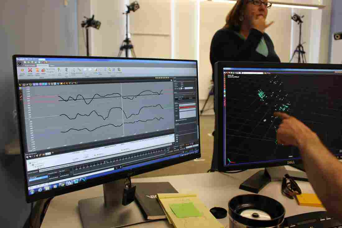 Jason Lamberton, ML2's tech consultant, points to the motion capture marker's position on screen. The left screen displays a graph featuring the temporal rhythms of a simple nursery rhyme suited for a 6- to 18-month-old: a boat on a wave.