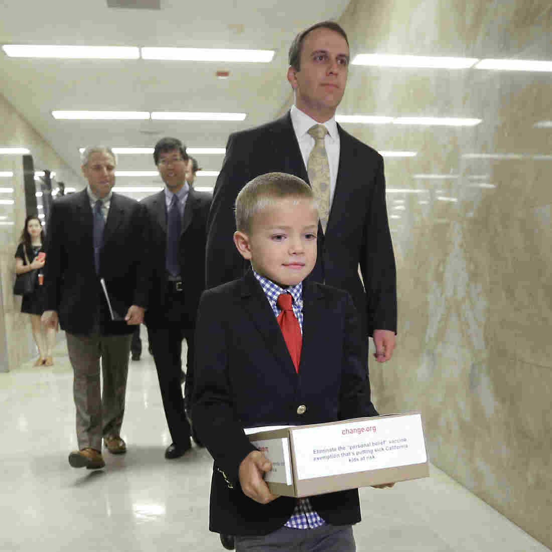 """Leukemia survivor Rhett Krawitt, 7, carries a box of petitions representing more than 30,000 people supporting a measure requiring nearly all California schoolchildren to be vaccinated. He took them to the governor's office at the Capitol in Sacramento, Calif., on Wednesday. The state Assembly voted Thursday to remove so-called """"personal belief exemptions"""" for immunizations."""