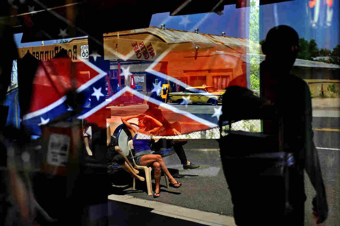 A Confederate flag is reflected in the window of a gift shop that sells them in Seligman, Ariz.